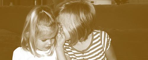 Two little girls telling secrets