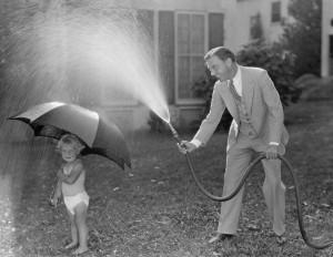 A man spraying a hose at a little kid with an umbrella