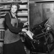 A woman standing at some type of machinery