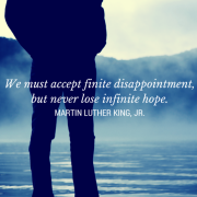 Person standing on the edge of a lake - We must accept finite disappointment, bet never lose infinite hope. - Martin Luther Kind, JR.