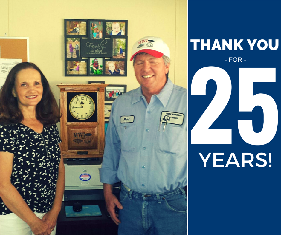 Mark and Kathi Wilkinson proudly standing in an office of a shop with a time clock in the background.