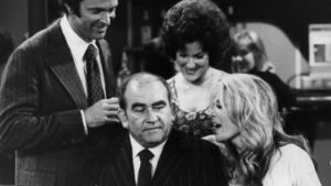 Lou Grant surrounded by employees