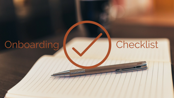 Notepad sitting on a table with a pen sitting on top of the notepad. Title - Onboarding Checklist (with large checkmark)