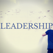 Person writing on a white board. Title - Leadership