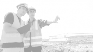 Two guys in safety vests and hard hats with a clipboard pointing at something on a worksite.