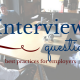 Five guys sitting around a conference table smiling at each other. Title - Interview questions best practices for employers