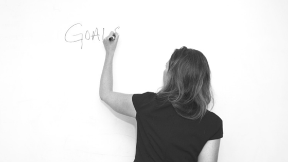 Person writing on a whiteboard. The word on the whiteboard is GOALS