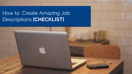 Desk with laptop on wooden table and smartphone next to it and title - How to Create Amazing Job Descriptions [CHECKLIST]