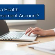 Hand moving the mouse on a laptop computer with title - What Is A Health Reimbursement Account