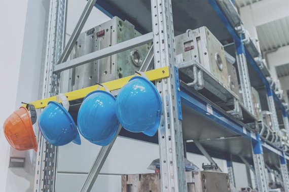 Close-up of protective helmets hanging in distributional warehouse of large automobile factory.