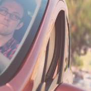 image of man driving red car and he is looking out the driver's side window he's wearing a watch and red checkered shirt