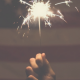 photo of a hand holding a lit sparkler in front of an american flag
