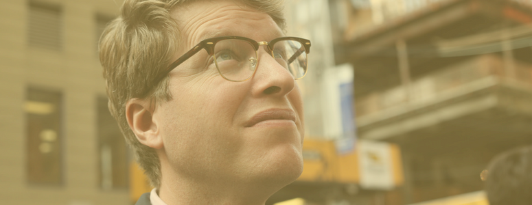 image of a man with half-rimmed glasses looking up. He is standing in a city setting. Image has a yellow tint over the picture