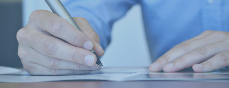 image of hands holding a pen on paper at a desk. photo has a transparent blue filter over it