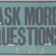 "Image of a sign that says, ""Ask more questions."" Sign is on a wall in-between two clocks"