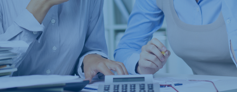image of two business women sitting at a desk looking at paper with pencils and a calculator