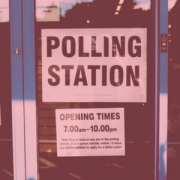 "Image of glass doors in front of building. Sign on door says, ""polling station"""